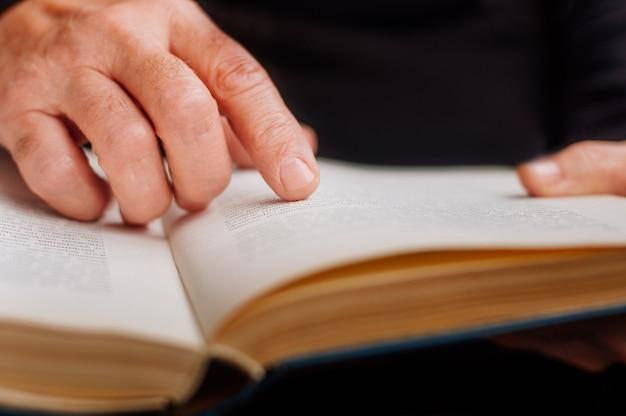 Человек читает книгу после текста с пальцем