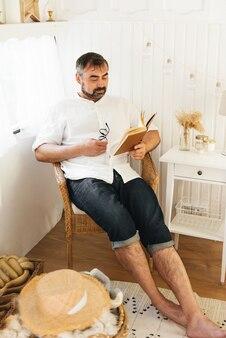 寝室で本を読んでいる男