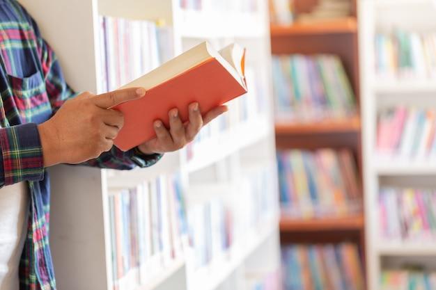 Человек читает. книга в его руках в библиотеке.