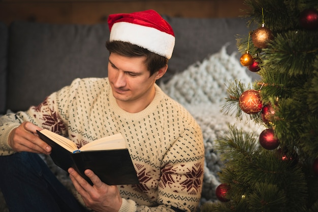 Man reading a book near christmas tree