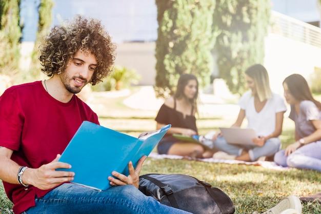 Man reading book near friends in park