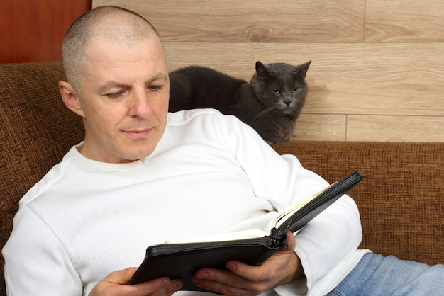 Man reading a book relaxing on the couch with the cat