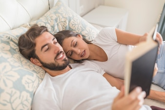 Man reading book to sleeping girlfriend