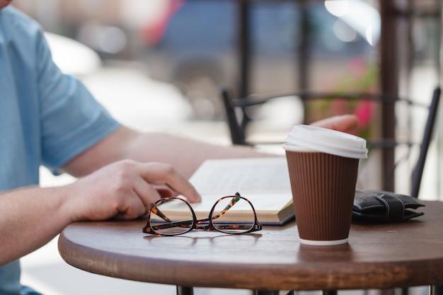 Человек читает книгу с кофе или чаем