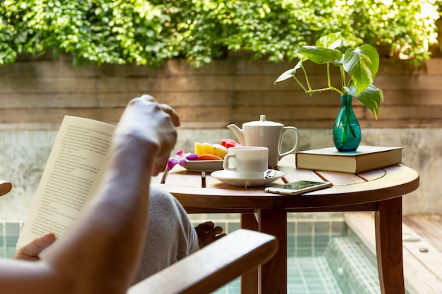Man reading a book with cup of coffee and fresh fruit on wooden table.