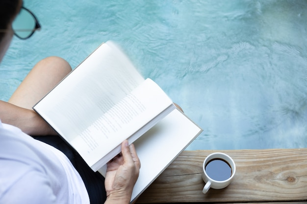 Man reading book with cup of coffee on wooden floor next to swimming pool.