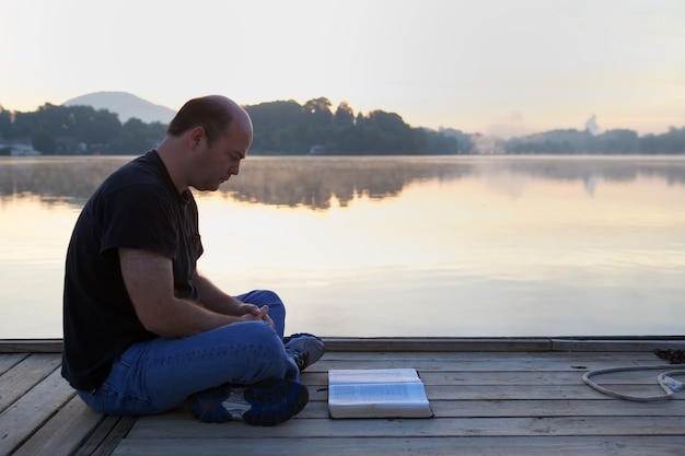 Man reading a book on a wooden bridge surrounded by hills and a lake under the sunlight