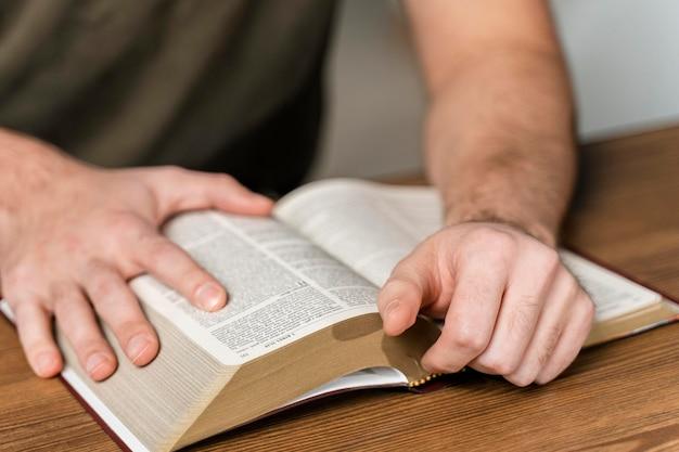 Uomo che legge dalla bibbia sul tavolo