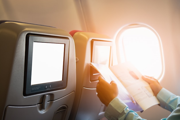 Man reading magazine on airplane seat with individual lcd screen