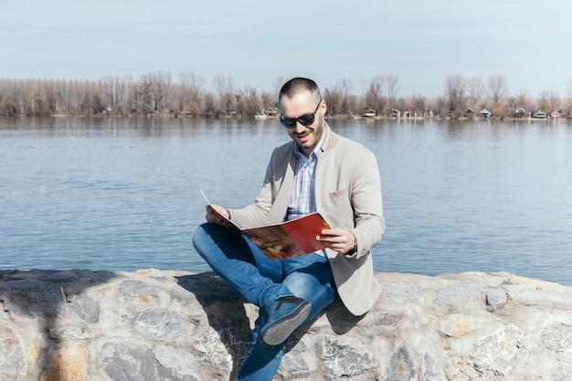 Man reading magazine near water