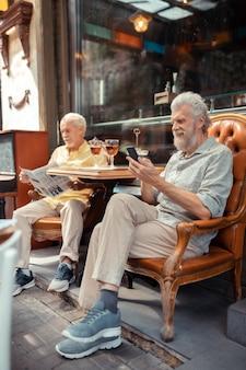 남자 읽기 메시지입니다. 친구와 밖에 앉아 있는 동안 스마트폰으로 메시지를 읽는 수염 난 은퇴한 남자