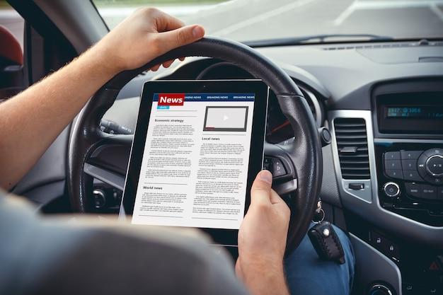 자동차의 바퀴에 손에 태블릿으로 뉴스를 읽는 남자