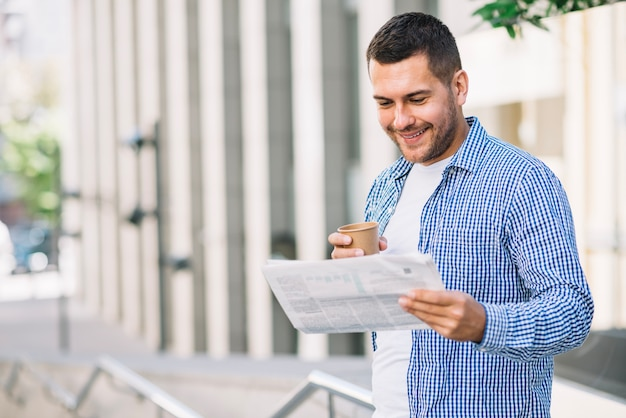 Man reading newspaper near building