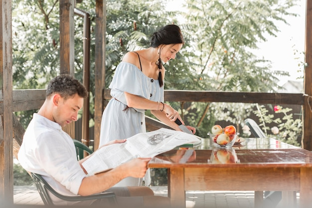 Man reading newspaper with his wife cutting fruits at outdoor garden