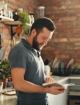 Uomo che legge un libro di ricette in cucina