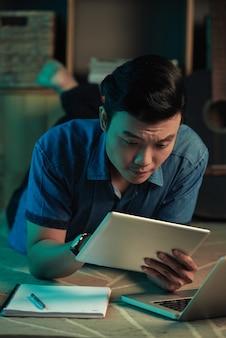 태블릿에 뭔가 읽는 남자