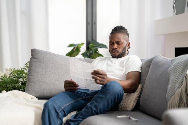 自宅でcovidテストの指示を読んでいる男