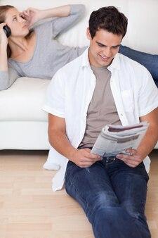 彼のガールフレンドがソファで音楽を聴いている間にニュースを読んでいる男