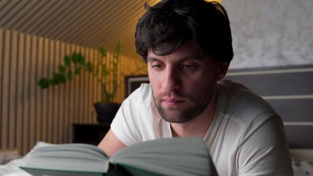 남자는 침대에서 저녁에 집에서 책을 읽습니다.