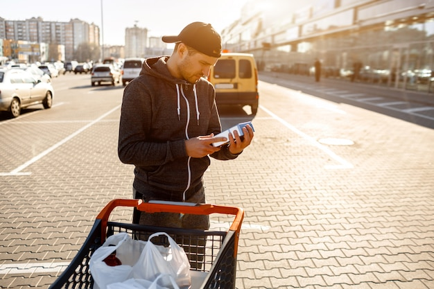A man reads the composition of food ingredients on the packaging in the parking lot of a shopping mall or supermarket.
