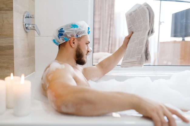 Man reads newspaper in bath with foam, morning hygiene. male person relax in bathroom, skin and body treatments procedures