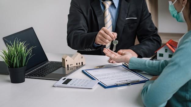 남자 부동산 중개인은 사무실에서 성공적인 계약을 맺은 고객에게 집 열쇠를 건네줍니다.