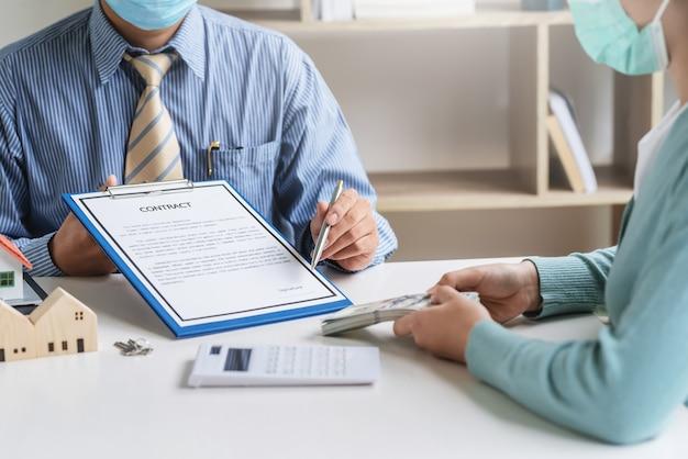 住宅購入契約の契約書を指すペンを持っている男性の不動産業者は、オフィスでお金を持っている顧客と相互に合意します。