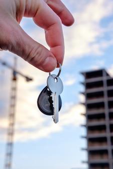 Man realtor offering keys from new house hand closeup