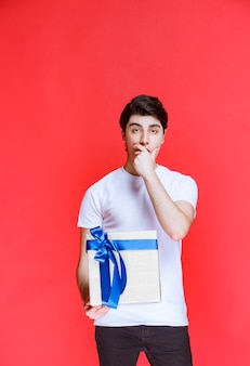 Man received a white gift box and looks surprized