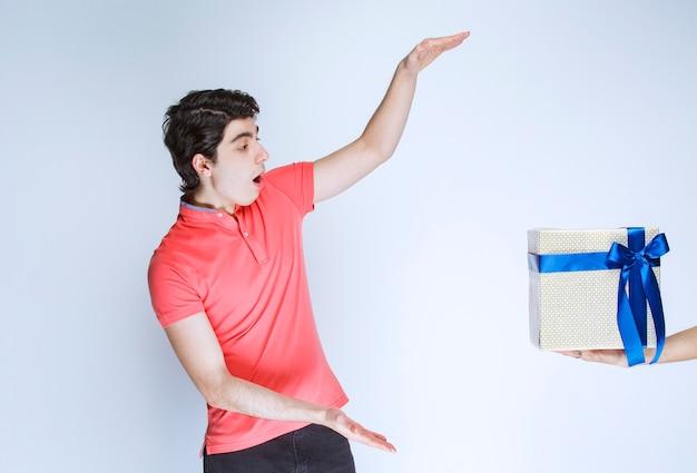 두 손으로 파란색 리본으로 싸여 흰색 선물 상자를 받고 들고 남자