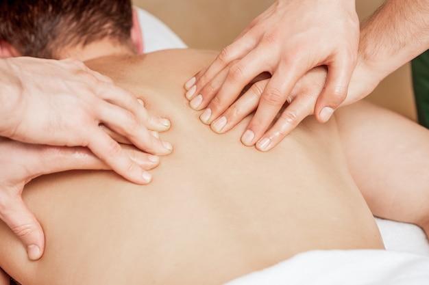 Мужчина получает массаж спины в четырех руках двух терапевтов-мужчин крупным планом.