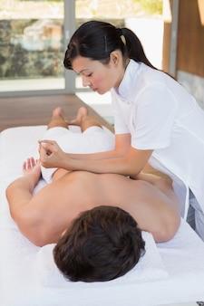 Man receiving back massage at spa center