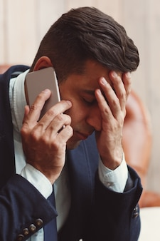 Man receiving bad news on the phone.