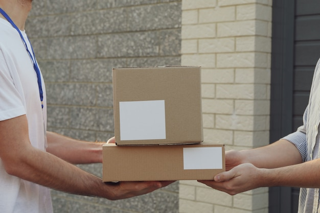 Man receiving boxes from delivery man outdoor, blank space