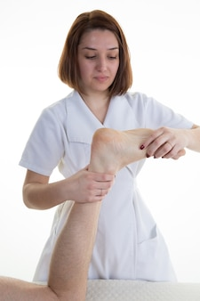 Человек, получающий рефлексотерапию ноги, улыбающийся женский терапевт