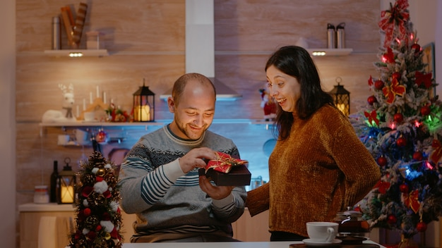 Man receiving gift from woman on christmas eve day