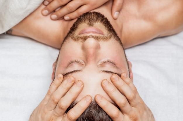 Мужчина получает массаж головы двумя массажистами