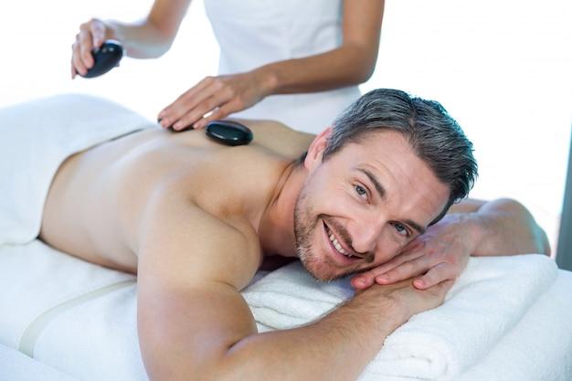 Man receiving a hot stone massage from masseur