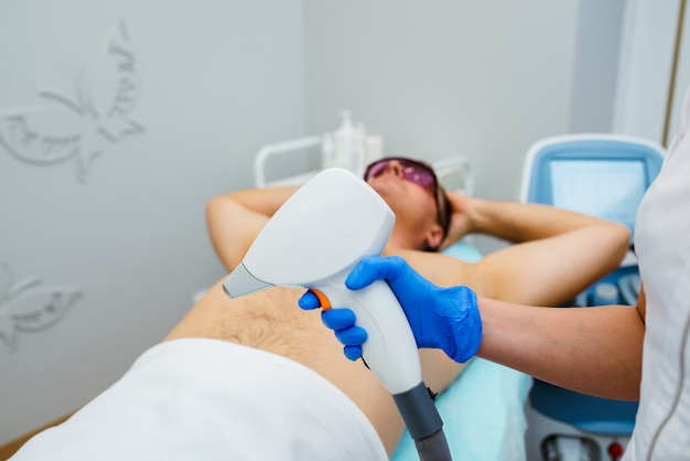 Man receiving laser epilation at armpit on beauty center
