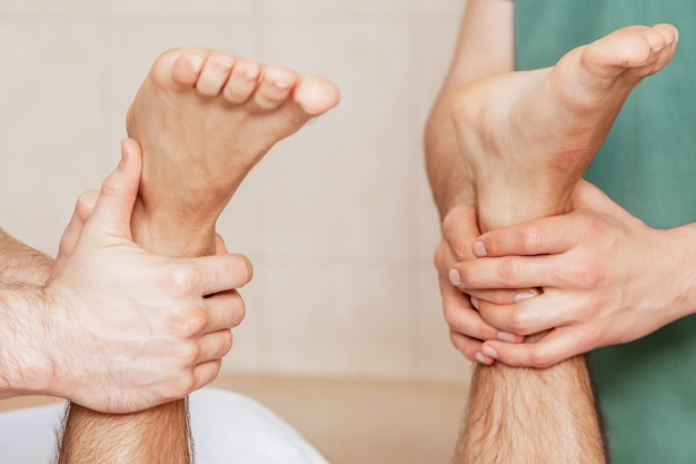 Man receiving leg massage on his feet by two massage therapists, close up.