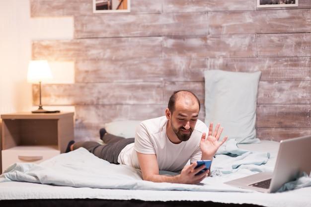 Uomo che riceve una videochiamata a tarda notte mentre si rilassa in camera da letto