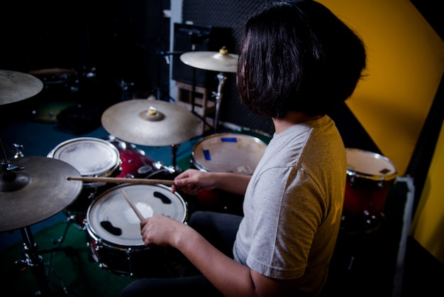 Man recording music on drum set in studio