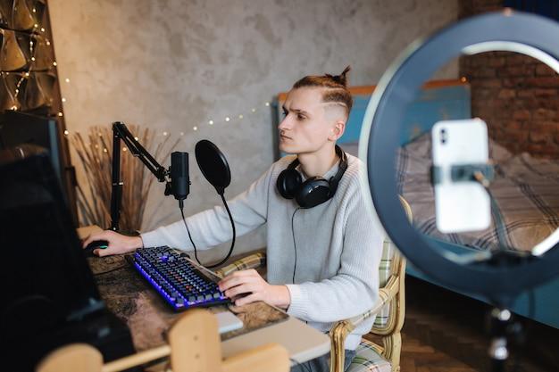 컴퓨터에 집에서 작업하는 동안 스마트 폰에 비디오를 녹화하는 사람