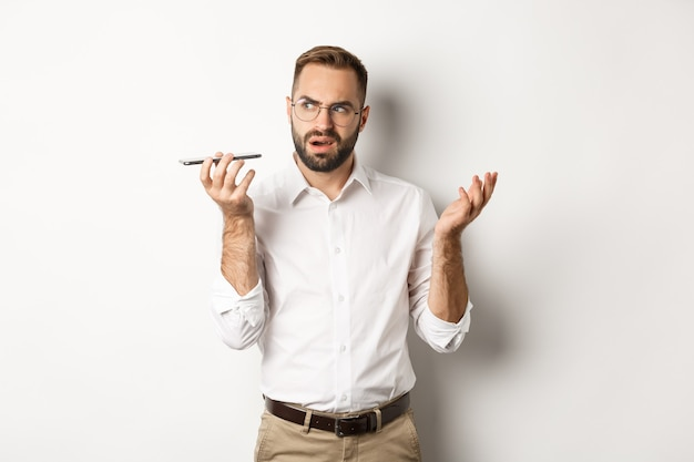 음성 메시지를 녹음하거나 스피커폰에 얘기하는 사람, 혼란스러워 보이는, 흰색 배경 위에 서.