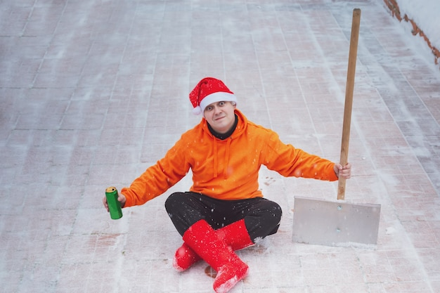 Man in a red christmas hat and red winter boots in an orange sweater is sitting in a lotus