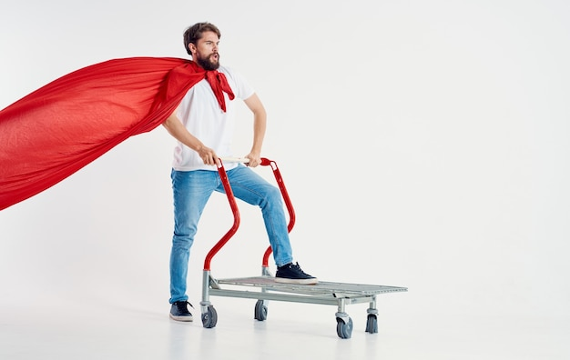 Man in a red coat jeans t-shirt cargo trolley light background copy space