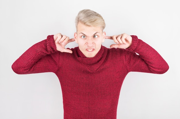 Man in a red home sweater plug his ears with his fingers against the loud noise.