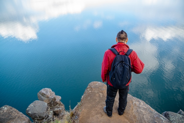 A man in a red jacket and black leotards with a backpack. the guy stands on the edge of a cliff and looks into the water. clouds reflected in water.