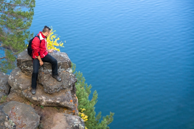 A man in a red jacket and black tights with a backpack sits on large stones on the edge of a cliff and looks down on the sea surface.