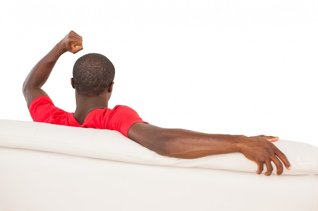 Man in red jersey sitting on couch cheering